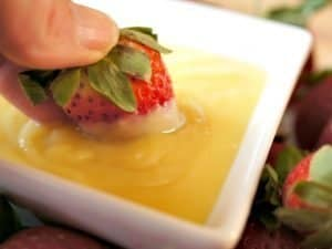 Dipping strawberries in pineapple curd